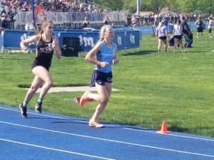 Panorama freshman Ella Waddle (blue shirt) holds off AC/GC sophomore Kate Crawford during the second lap of the 3000 meter run at the Van Meter State Qualifying Meet. Photo by RVR's Nate Gonner.