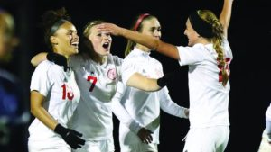 ADM grad Sydney Bertman (No. 7) celebrates with her teammates after scoring the go-ahead goal against the Peru State Bobcats on October 6. Photo courtesy of Grand View University Athletics.