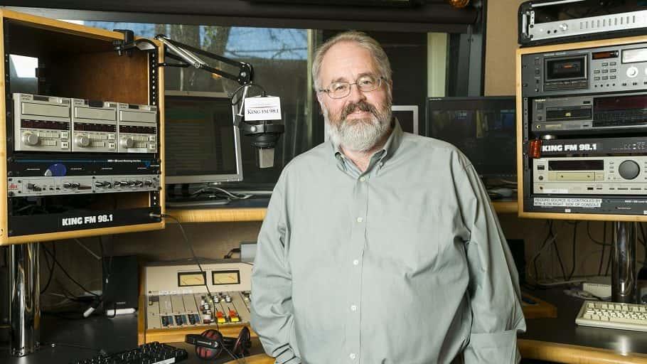 Man stands inside radio broadcast studio