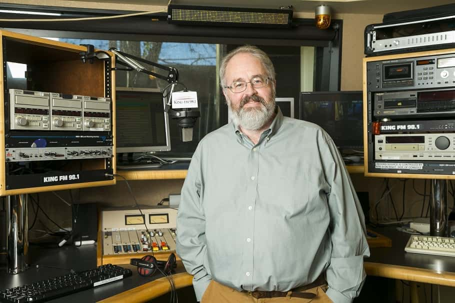 Man stands inside radio broadcast studio