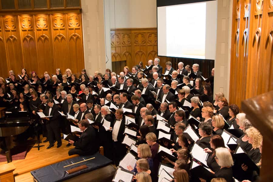 Large chorus sings on altar inside wood-paneled church