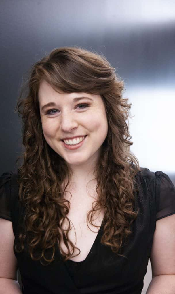 Woman with brown curly hair smiling at camera