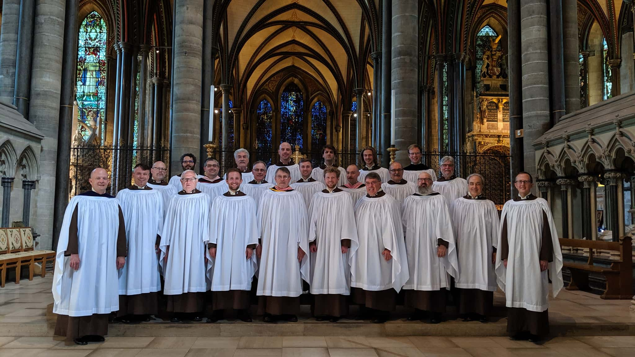 Church choir in white robes inside of a large cathedral