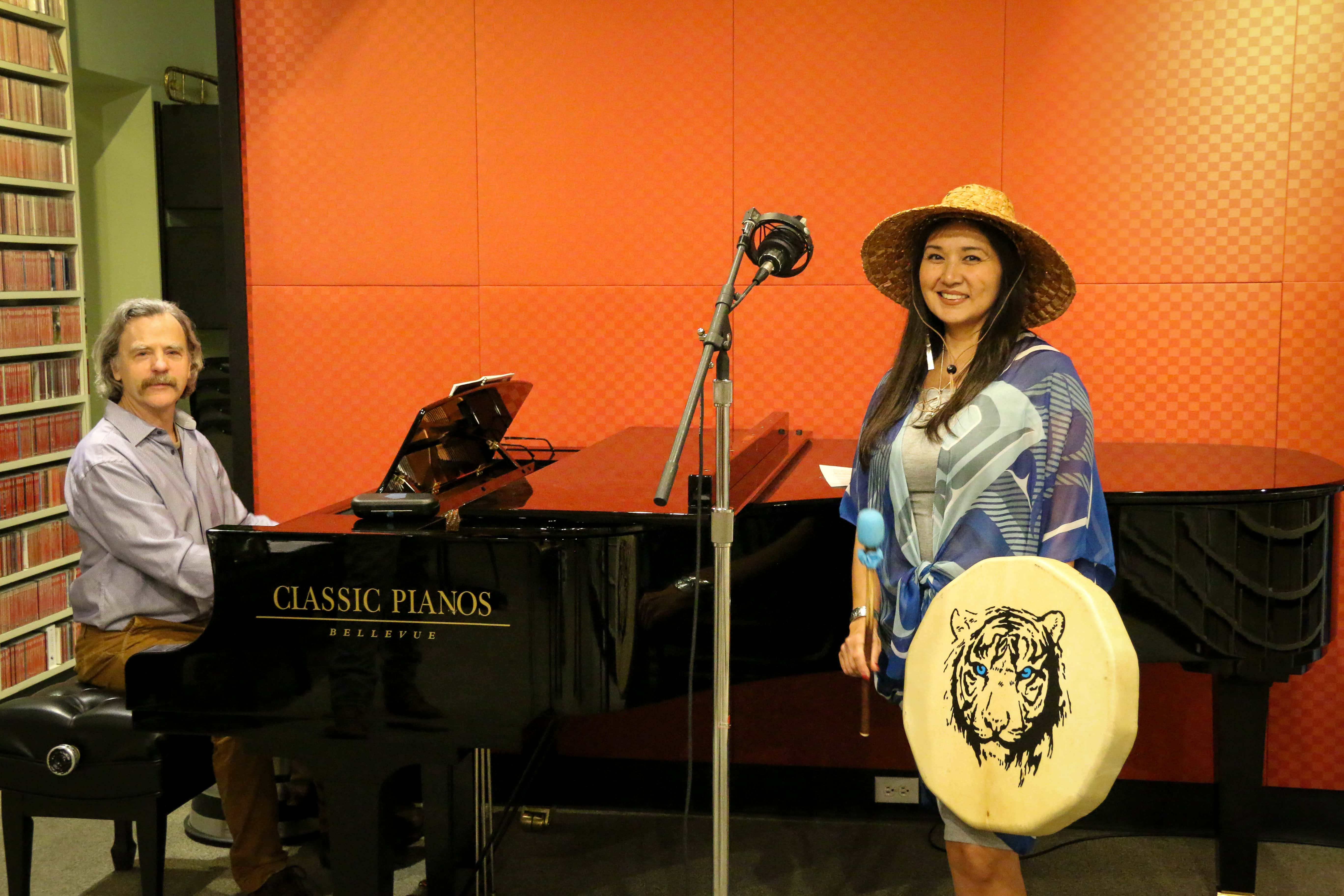 Woman in Alaska Native attire stands near a microphone, holding a drum, with a man seated next to her at a grand piano