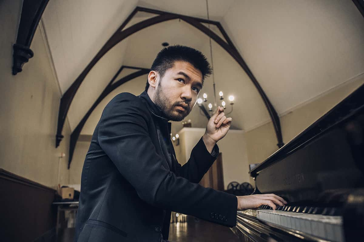 Close-up of man in black suit sitting at piano inside vaulted, high-ceiling room