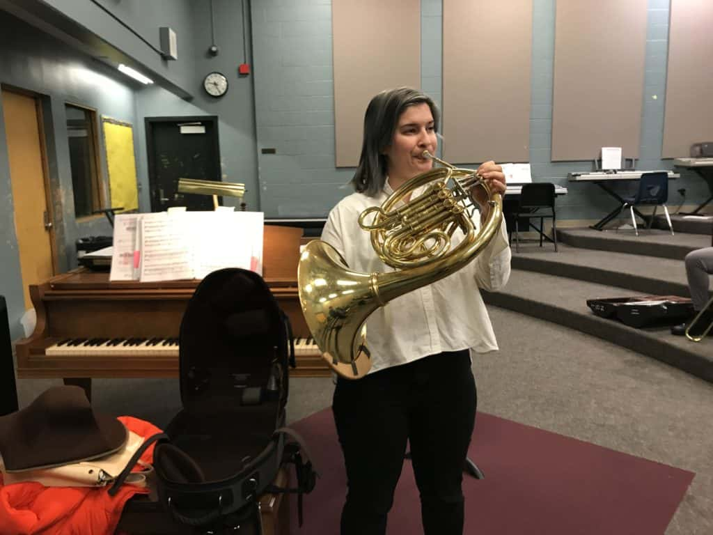 Woman stands inside music classroom, playing a French horn