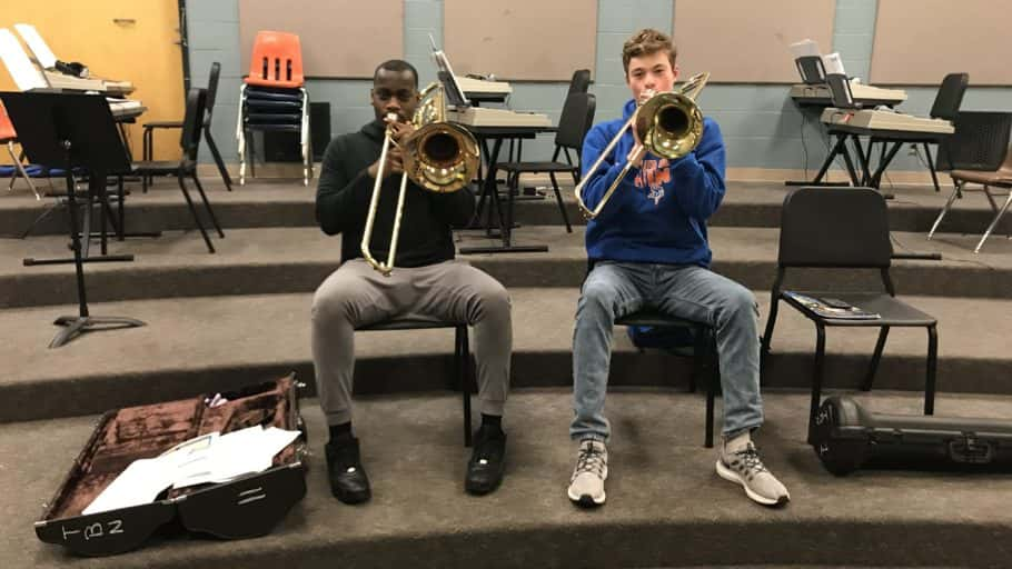 Two young men play trombone.