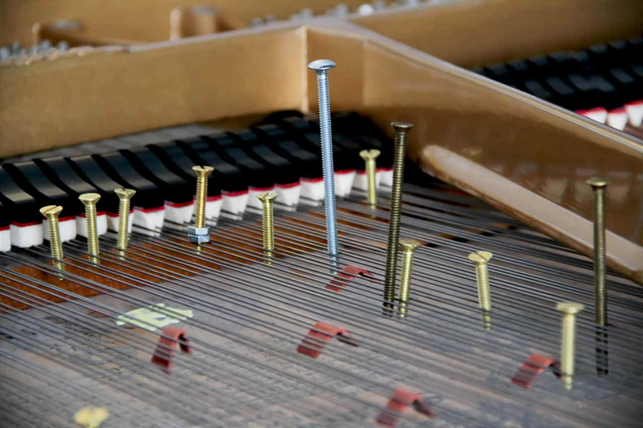 "A close-up of a piano's strings into which screws have been inserted to make it a ""prepared piano."""