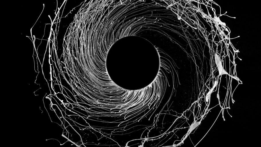 Swirling white liquid against a black background