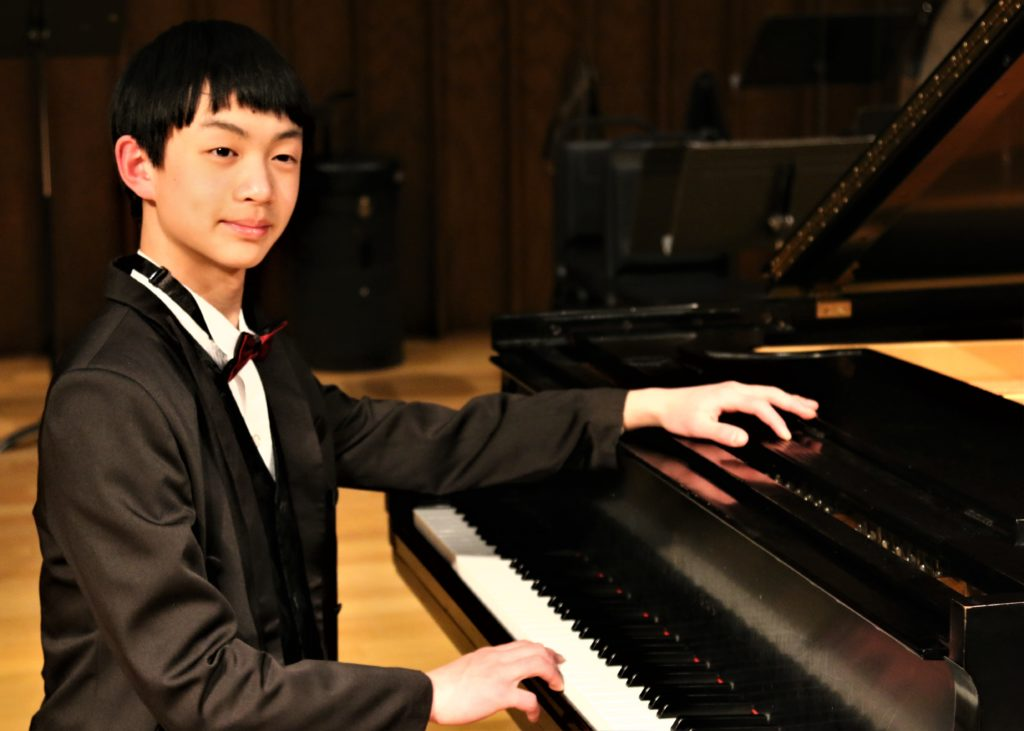 Young man in tuxedo sits at grand piano