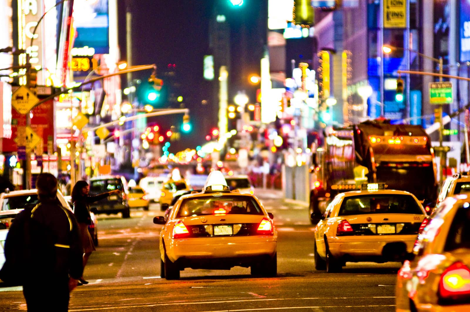 Nighttime photograph of taxicabs on the street in Times Square, New York City