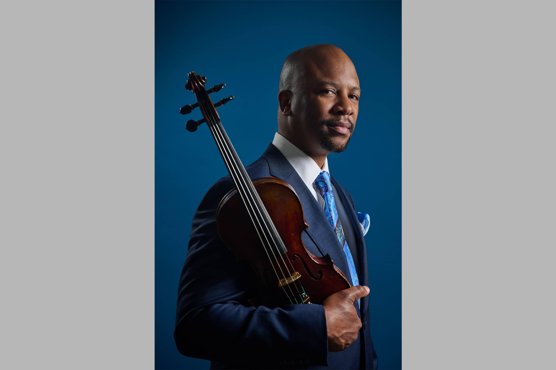 Portrait of Dr. Quinton Morris, holding a violin