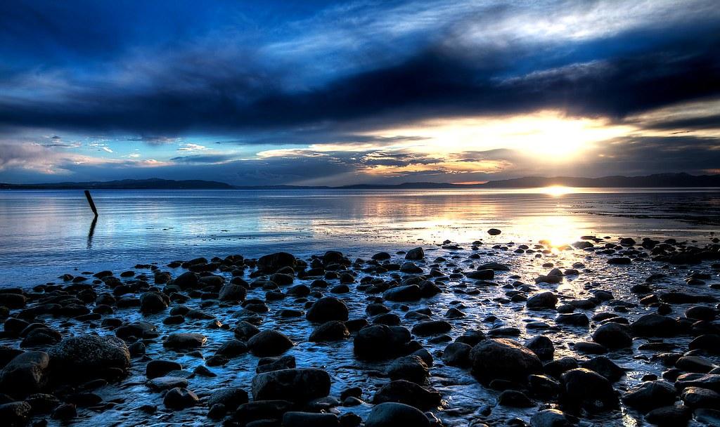 Photo of rocks along an ocean coastline at sunset
