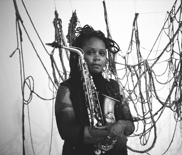 Woman holding saxophone in front of artwork
