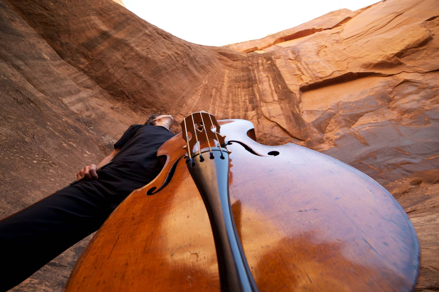 Close-up view of upright bass with man standing behind, and tall rock formation beyond (photo by Gabriel Gomez)