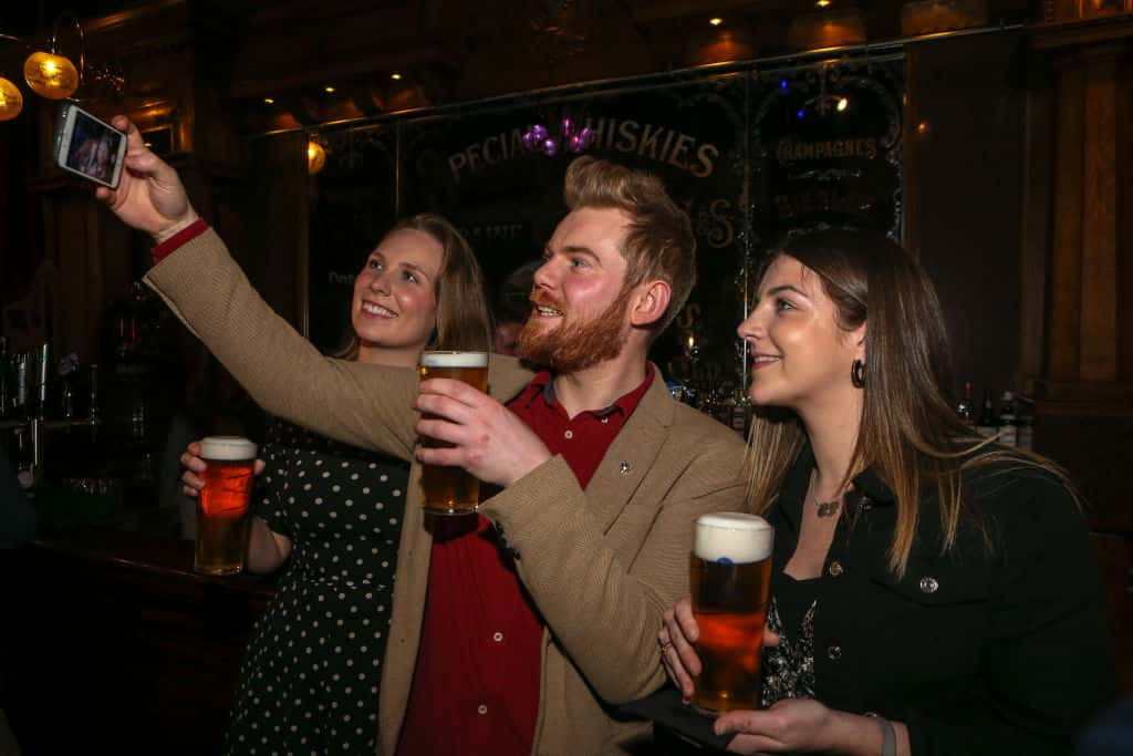 Guy and two girls doing a toast with beer
