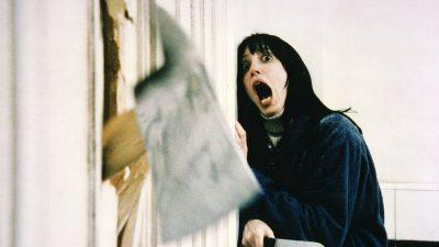 Woman scared watchin an axe go through a door