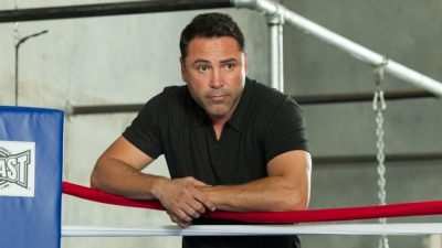 Oscar de la Hoya standing and resting his arms on a boxing ring's turnbuckle padding.