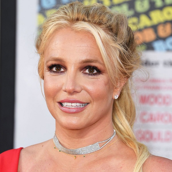 Britney Spears smiling on a red carpet.