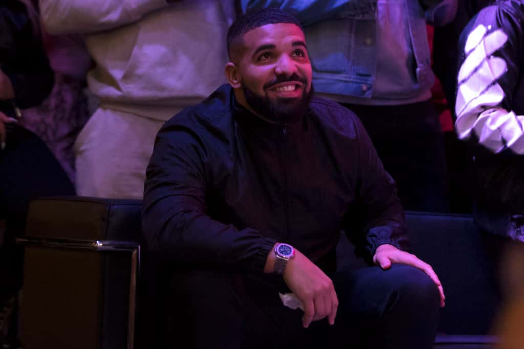 Drake sitting down wearing a black suit