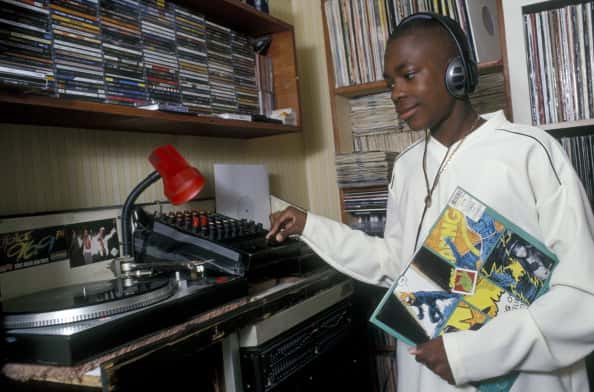 14 year old boy listening to music in his bedroom, Brixton, South London