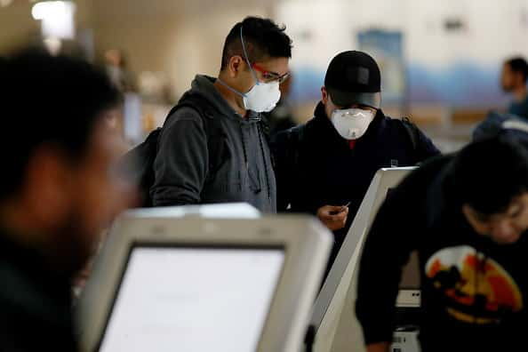 A passenger checks in for an American Airlines in Terminal D at Dallas/Fort Worth International Airport (DFW) on March 13, 2020 in Dallas, Texas. American Airlines announced that it is cutting a third of its international flights amid a major slowdown due to the Coronavirus (COVID-19) outbreak.