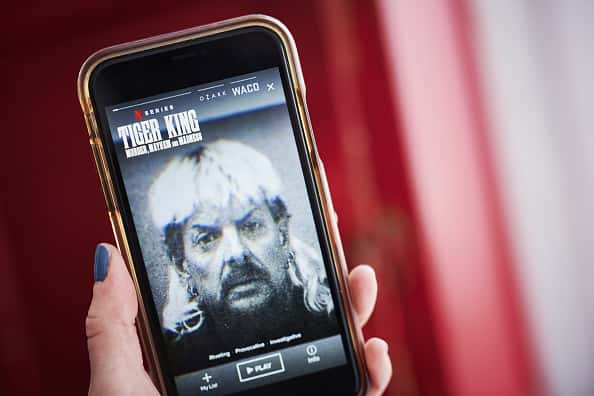 """The Netflix Inc. true crime documentary miniseries """"Tiger King"""" trailer is displayed on a smartphone in an arranged photograph taken in the Brooklyn Borough of New York, U.S., on Monday, April 20, 2020. Netflix Inc. is riding a wave of optimism as it heads into its earnings report Tuesday, with investors pushing the shares tonew highsand analysts seeing people download its app in record numbers."""