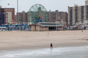 A pedestrian walks on the beach at Coney Island in the Brooklyn borough of New York, U.S., on Monday, April 20, 2020. Mayor Bill De Blasio has ordered all citypoolsand beaches shut down for the summer.