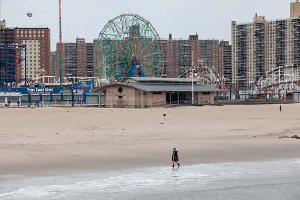 A pedestrian walks on the beach at Coney Island in the Brooklyn borough of New York, U.S., on Monday, April 20, 2020. Mayor Bill De Blasio has ordered all city pools and beaches shut down for the summer.