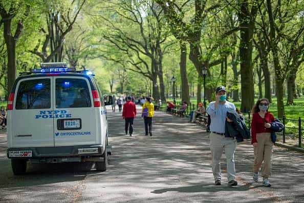 People wearing masks walk past an NYPD vehicle driving through pedestrian walkways announcing over the loud speaker to say '6 feet apart' in Central Park amid the coronavirus pandemic on May 3, 2020 in New York City. COVID-19 has spread to most countries around the world, claiming over 248,000 lives with over 3.4 million cases.