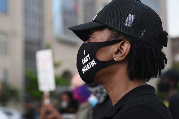 "ST LOUIS, MO - MAY 28: A protestor looks on as a crowd gathers outside the St. Louis Police Department Headquarters on May 28, 2020 in St Louis, Missouri. Rallies have erupted nationwide in response to the killing of George Floyd by a Minneapolis police officer. Four Minneapolis police officers have been fired after a video taken by a bystander was posted on social media showing Floyd's neck being pinned to the ground by the officer as he repeatedly said, ""I can't breathe"". Floyd was later pronounced dead while in police custody after being transported to Hennepin County Medical Center."