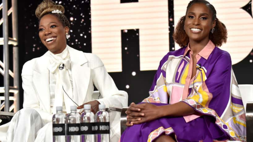 Yvonne Orji and Issa Rae smiling at the camera while sitting on stage