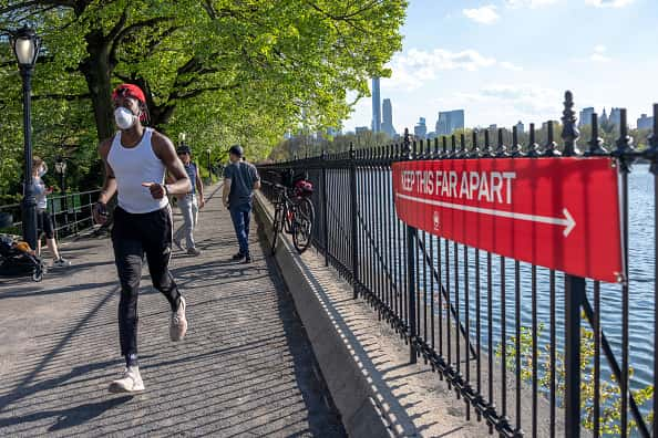 "NEW YORK, NEW YORK - MAY 03: A man wearing a mask runs near a sign that says, ""Keep this far apart"" in Central Park as temperatures rise amid the coronavirus pandemic on May 3, 2020 in New York City. COVID-19 has spread to most countries around the world, claiming over 248,000 lives with over 3.4 million cases"
