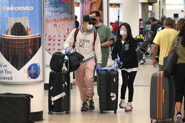 People navigate through Miami International Airport amid coronavirus fears on March 15, 2020 in Miami, Florida. Airline companies have seen travelers canceling or moving up return dates as people protect themselves against the possibility of catching COVID-19.