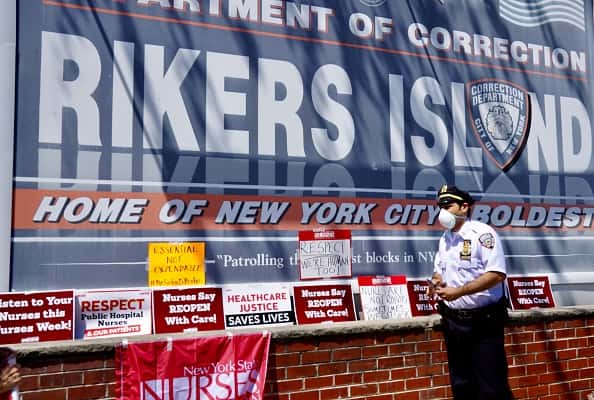 A correctional officer asks protesters during the nurses protest to not cover the main entrance with signs at Rikers Island Prison on May 7, 2020 in New York City. By the end of last month, more than 1,300 people in the city's jail system had tested positive for COVID-19, according to the Department of Corrections. One prisoner who died from the virus, Raymond Rivera, was being held on a parole violation at Rikers, the city's largest jail complex.
