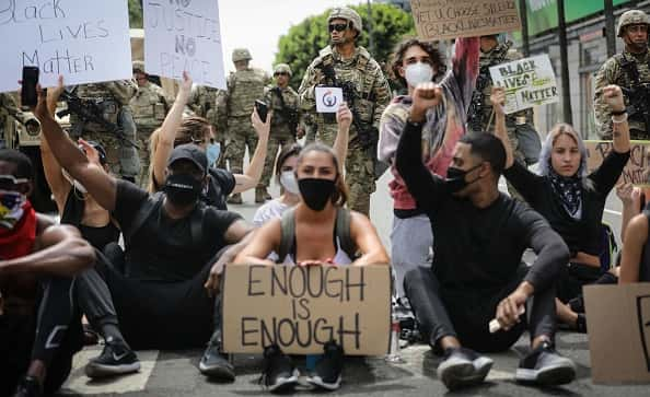 Protesters chant as National Guard troops keep watch during a peaceful demonstration over George Floyd's death on Sunset Boulevard in Hollywood on June 2, 2020 in Los Angeles, California. California Governor Gavin Newsom has deployed National Guard troops to Los Angeles County to curb unrest which occurred amid some demonstrations. Former Minneapolis police officer Derek Chauvin was taken into custody for Floyd's death and charged with third-degree murder.