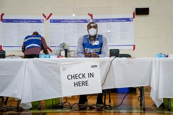 An election official wears a mask and sits behind a plastic barrier as he waits to check in voters at a polling place at McKinley Technology High School during primary election day on June 2, 2020 in Washington, DC. On Tuesday, nine states and the District of Columbia are holding primaries, most of which were previously delayed due to the coronavirus pandemic.