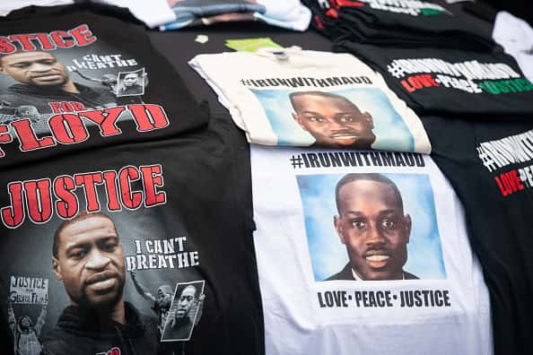 T-shirts memorializing George Floyd and Ahmaud Arbery are displayed for sale on a car hood outside the Glynn County courthouse during a court appearance by Gregory and Travis McMichael, two suspects in the fatal shooting of Ahmaud Arbery, on June 4, 2020 in Brunswick, Georgia. Arbery was killed on February 23.