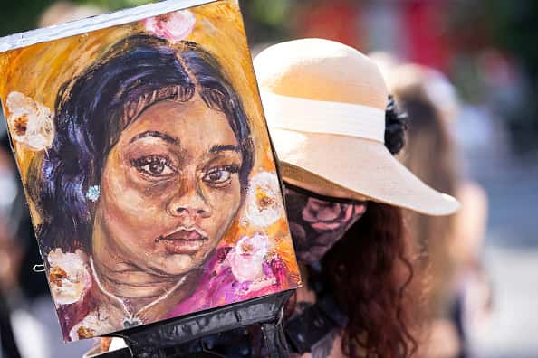 "Artist Claudine Anrather wearing a mask holds her hand painted sign tribute to Breonna Taylor in Union Square Park, New York. This was the day after protesters have being taken by federal agents without badges and put into unmarked vehicles while others have been beaten and pepper sprayed in Portland. The protest organized by NYC Revolution Club is demanding Trump/Pence Out Now and an end to NYPD Violence Against Protesters. It is also a call for an end to what is believed to be fascist tactics by the Trump Administration to maintain order. Protesters continue taking to the streets across America and around the world after the killing of George Floyd at the hands of a white police officer Derek Chauvin that was kneeling on his neck during for eight minutes, was caught on video and went viral. During his arrest as Floyd pleaded, ""I Can't Breathe"". The protest are attempting to give a voice to the need for human rights for African American's and to stop police brutality against people of color. They are also protesting deep-seated racism in America. Many people were wearing masks and observing social distancing due to the coronavirus pandemic. Photographed in the Manhattan Borough of New York on July 18, 2020, USA."