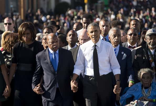 US President Barack Obama walks alongside Amelia Boynton Robinson (R), one of the original marchers, the Reverend Al Sharpton (2nd R), First Lady Michelle Obama (L), and US Representative John Lewis (2nd-L), Democrat of Georgia, and also one of the original marchers, across the Edmund Pettus Bridge to mark the 50th Anniversary of the Selma to Montgomery civil rights marches in Selma, Alabama, March 7, 2015. The event commemorates Bloody Sunday, when civil rights marchers attempting to walk to the Alabama capital of Montgomery to end voting discrimination against African Americans, clashed with police on the bridge. AFP PHOTO / SAUL LOEB