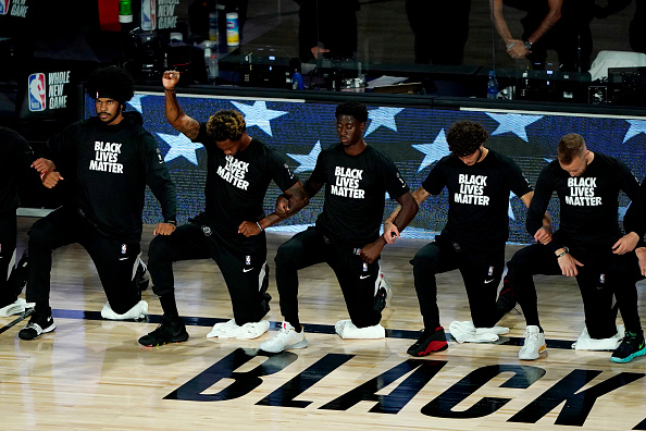 Lance Thomas of the Brooklyn Nets gestures as he and teammates kneel in honor of the Black Lives Matter movement prior to an NBA basketball game against the Portland Trail Blazers at AdventHealth Arena at ESPN Wide World Of Sports Complex on August 13, 2020 in Lake Buena Vista, Florida. NOTE TO USER: User expressly acknowledges and agrees that, by downloading and or using this photograph, User is consenting to the terms and conditions of the Getty Images License Agreement.