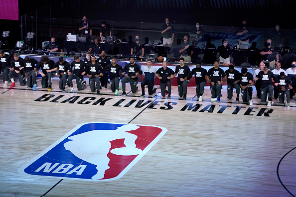 Members of the Milwaukee Bucks and the Boston Celtics kneel around a Black Lives Matter logo before the start of an NBA basketball game Friday, July 31, 2020, in Lake Buena Vista, Florida. NOTE TO USER: User expressly acknowledges and agrees that, by downloading and or using this photograph, User is consenting to the terms and conditions of the Getty Images License Agreement.