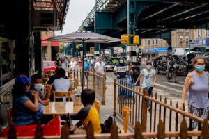 Pedestrians wearing protective masks pass in front of customers sitting outside to eat at a restaurant in the Corona neighborhood in the Queens borough of New York, U.S., on Saturday, June 27, 2020. New York's public transport usage has risen to almost half the typical level before the coronavirus outbreak, a recovery that has yet to extend to the restaurant industry.