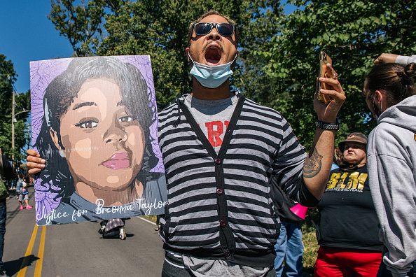 A demonstrator holds up a sign of Breonna Taylor while chanting during a protest in wake of Supreme Court Justice Ruth Bader Ginsburgs death in front of Senate Majority Leader Sen. Mitch McConnells home on September 19, 2020 in Louisville, Kentucky. People rallied in front of McConnells home to stand in solidarity for Breonna Taylor, and refute McConnells statement that if President Donald Trump nominates someone to take the place of Ginsburg following her death, the Senate would proceed with the nomination process despite the presidential election being less than six weeks away.