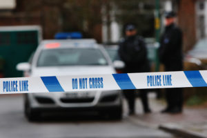 LONDON - DECEMBER 27: Police tape is pictured as police officers stand guard outside of a house in Edgeware on December 27, 2007 in London, England. A man is facing charges after a police officer was killed on duty after being called to a domestic row at an address in North London.