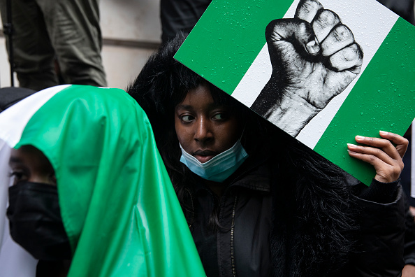 Protesters hold placards and signs calling for the end of police killings of the public in Nigeria, during a demonstration on October 21, 2020 in London, England. Nigerian police opened fire on protestors in Lagos yesterday after 12 days of anti-police demonstrating. Nigerians are protesting against police brutality carried out by a unit of the Nigerian police force called SARS (the Special Anti-Robbery Squad).