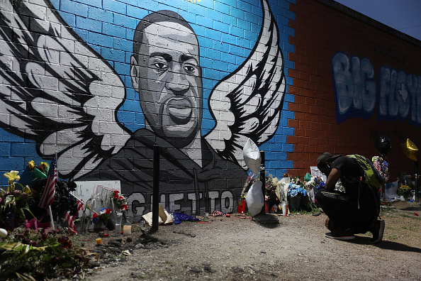HOUSTON, TEXAS - JUNE 08: Joshua Broussard kneels in front of a memorial and mural that honors George Floyd at the Scott Food Mart corner store in Houston's Third Ward where Mr. Floyd grew up on June 8, 2020 in Houston, Texas. The funeral and burial for George Floyd will be held June 9. Floyd died on May 25th while in Minneapolis police custody, sparking nationwide protests.