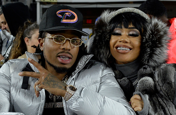 Rapper Quavo of Migos and Saweetie attend a football game between Baltimore Ravens and Los Angeles Rams at Los Angeles Memorial Coliseum on November 25, 2019 in Los Angeles, California.