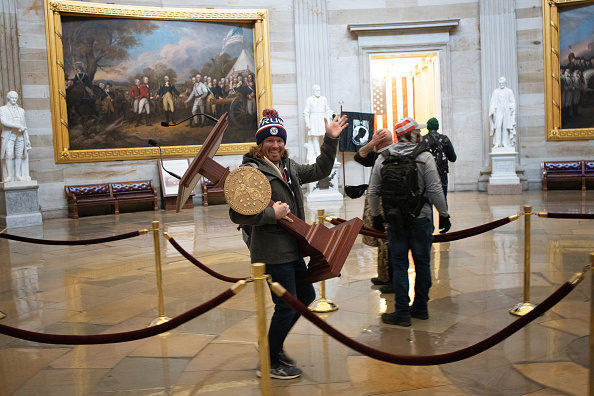 A pro-Trump protester carries the lectern of U.S. Speaker of the House Nancy Pelosi through the Roturnda of the U.S. Capitol Building after a pro-Trump mob stormed the building on January 06, 2021 in Washington, DC. Congress held a joint session today to ratify President-elect Joe Biden's 306-232 Electoral College win over President Donald Trump. A group of Republican senators said they would reject the Electoral College votes of several states unless Congress appointed a commission to audit the election results.