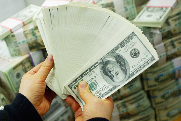 A South Korean banker carries US dollar bank notes at the Korea Exchange bank on February 22, 2005 in Seoul, South Korea. The South Korean won jumped to its highest intraday level in more than seven years in domestic trade on Tuesday, boosted by strong foreign equity buying and exporter deals.